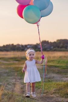Klein meisje in witte jurk met ballonnen buiten