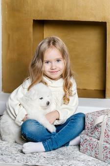 Klein meisje in witte kleren zit op de vloer in de buurt van de boom met witte samojeed puppy en lacht.