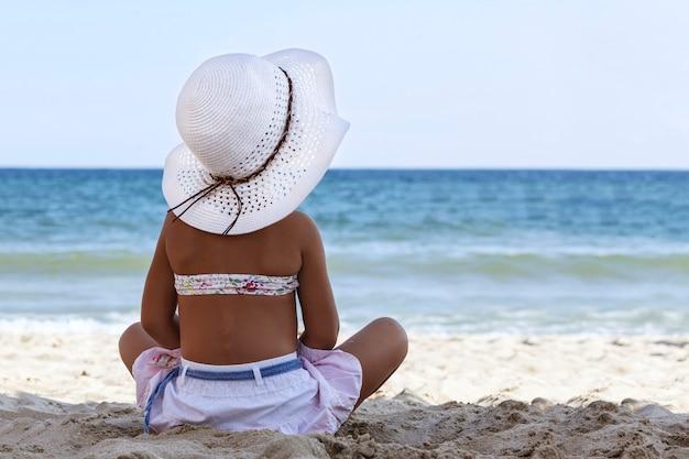 Klein meisje in witte strandhoed en bikini zit op zand aan zee met haar rug naar de camera