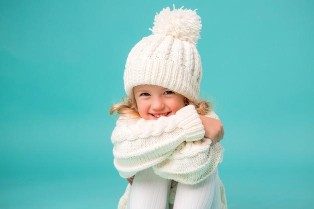 Klein meisje in witte winter gebreide muts en trui op blauw