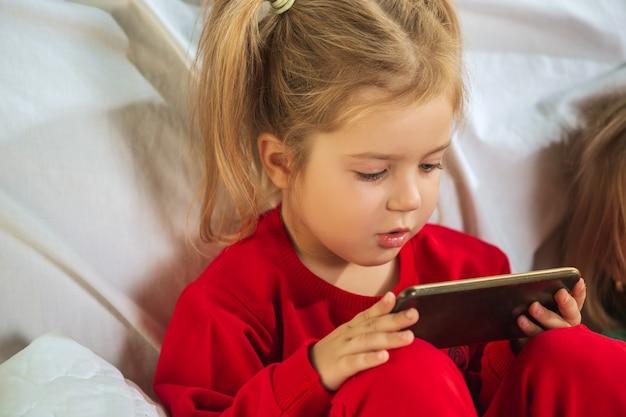 Klein meisje in zachte warme pyjama thuis spelen