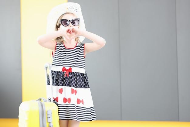 Klein meisje in zonnebril en hoed toont gebaar met haar handen in de vorm van een hart naast koffer