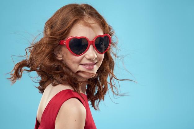 Klein meisje in zonnebril in de vorm van harten rode jurk krullend haar blauw