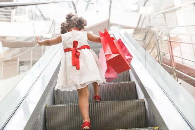 Klein meisje in zonnebril op de roltrap in het winkelcentrum met aankopen