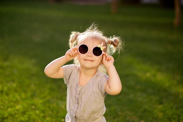 Klein meisje in zonnebril poseren in het park
