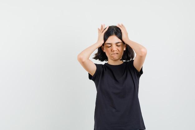 Klein meisje in zwart t-shirt hand in hand op het hoofd, lip bijten en op zoek vergeetachtig, vooraanzicht.