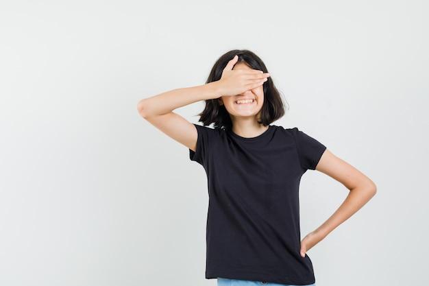 Klein meisje in zwart t-shirt met hand op de ogen en op zoek gelukkig, vooraanzicht.