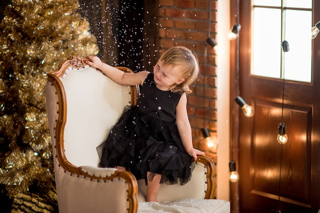 Klein meisje in zwarte jurk zit onder kerstversiering