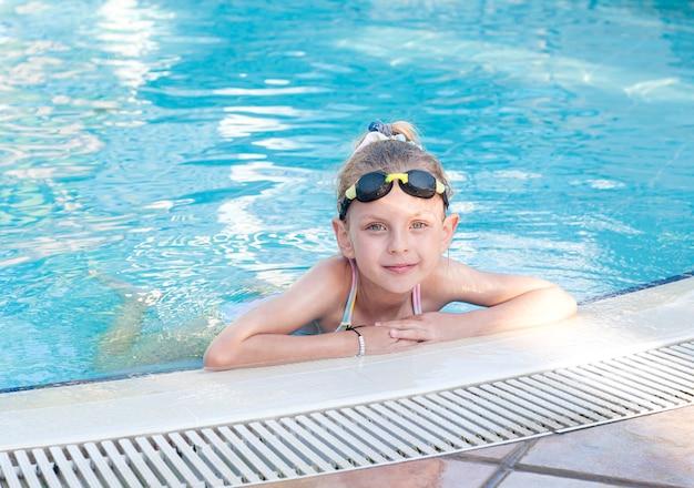 Klein meisje in zwembril zwemt in het zwembad