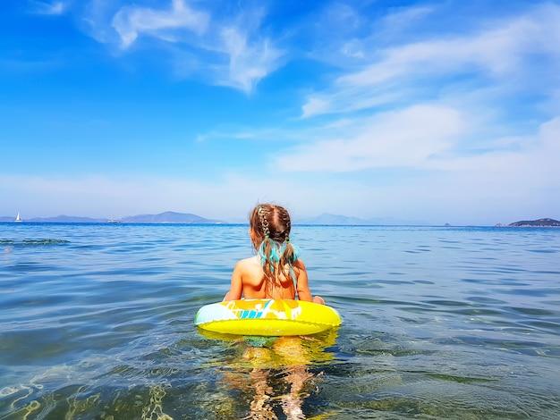 Klein meisje in zwemmen cirkel kijkt naar de zee. zomervakantie in de egeïsche zee, bodrum, turkije