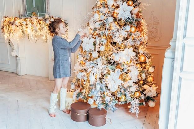 Klein meisje kerstboom thuis versieren