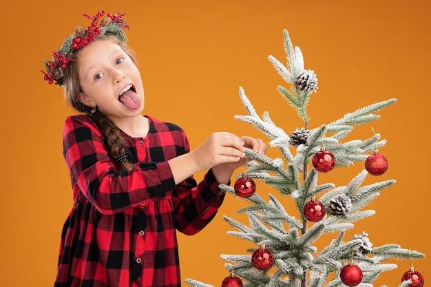 Klein meisje kerstkrans dragen in ingecheckte jurk kerstboom versieren gelukkig en vreugdevolle tong uitsteekt over oranje achtergrond