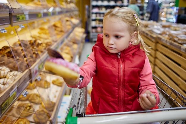Klein meisje kiest gebakjes in de supermarkt