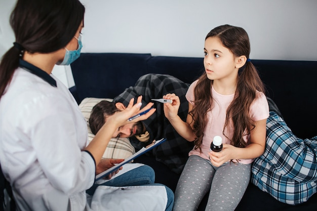 Klein meisje kijk naar vrouwelijke arts. ze houdt thermometer en fles siroop vast. meisje praat met dokter. zieke jonge man slapen op de bank. hij bedekt met deken.