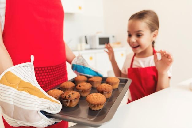 Klein meisje kijkt naar de afgewerkte cupcakes en heeft plezier.