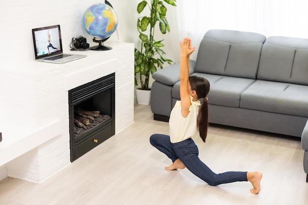 Klein meisje kijkt naar online video op laptop en doet thuis workout- of fitnessoefeningen in haar kamer. online training op afstand, zelfisolatie op sociale afstand, online onderwijsconcept