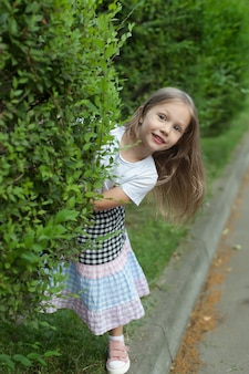 Klein meisje kijkt uit achter een boom in het park. rust in het park. mensen brengen tijd door in de natuur
