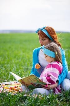 Klein meisje kind en moeder vrouw zitten op de sprei en lezen een boek met een sprookje, groen gras in het veld, zonnig lenteweer, glimlach en vreugde van het kind, blauwe lucht met wolken