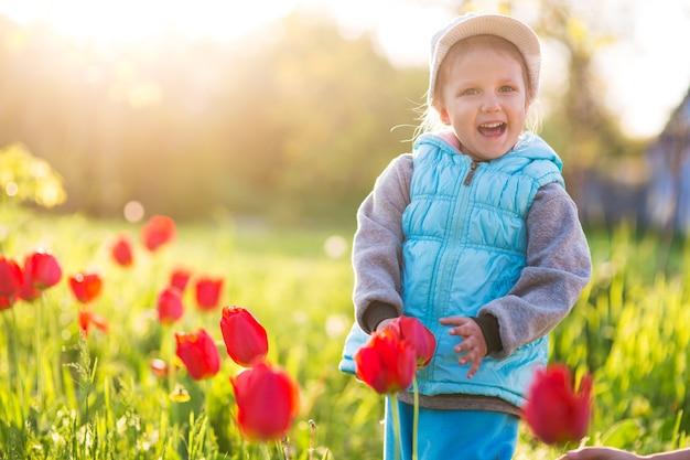 Klein meisje kind in een veld met groen gras en bloeiende tulpen bij zonsondergang