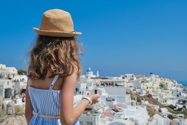 Klein meisje kind in jurk hoed staande terug en kijken naar het prachtige landschap van santorini