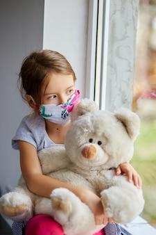 Klein meisje, kind in masker met teddybeer zit op ramen, coronavirus quarantaine