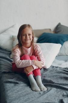 Klein meisje kind in roze kleren portret thuis.