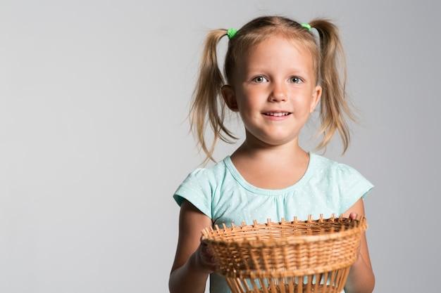Klein meisje kind met een lege mand in handen op een grijze achtergrond