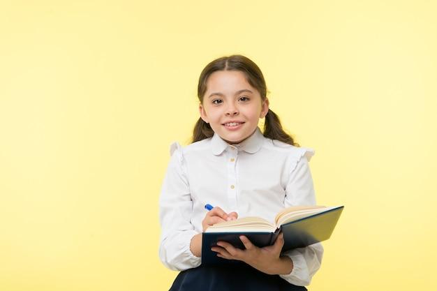 Klein meisje kind. privé lesgeven. gelukkig klein meisje in schooluniform. slim schoolmeisje. kinderdag. terug naar school. jeugd geluk. onderwijs online. student op examen.