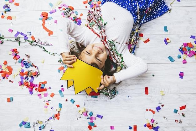 Klein meisje kind schattig en mooi met veelkleurige confetti op de vloer in een papieren kroon