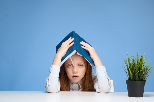 Klein meisje kind schoolmeisje huiswerk zittend aan een tafel