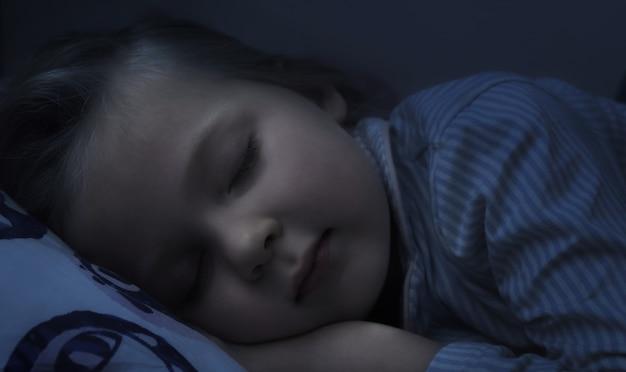 Klein meisje kind slaapt 's nachts zoet in het donker op een kussen in haar bed. kind droomt gezond slapen zonder te hoesten