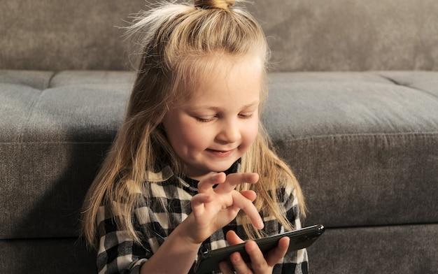 Klein meisje kind speelt mobiele spelletjes met behulp van telefoon. educatieve spellen en applicaties voor kinderen.