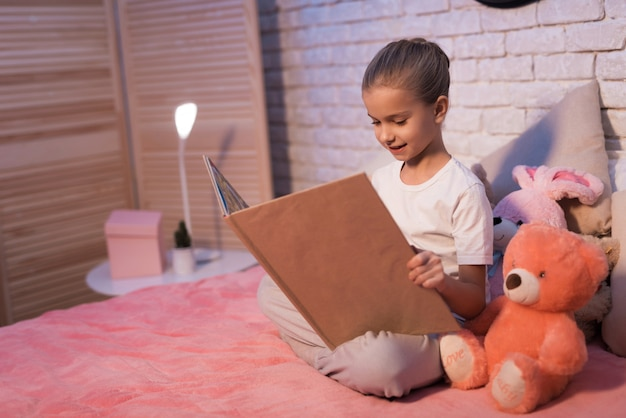 Klein meisje, kleindochter leest boek thuis 's nachts.