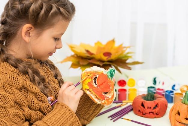 Klein meisje kleurt pompoenen voor een leuk halloween-feestje.