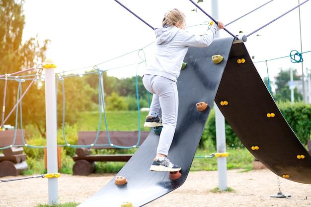 Klein meisje klimmen in een avonturenpark. het meisje houdt van klimmen in het avontuur van het touwparcours. klein meisje op de touw-hindernisbaan.