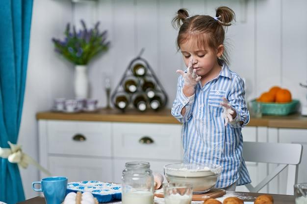 Klein meisje kneedt deeg in de keuken thuis. ze kookt koekjes met liefde en raakt haar neus aan.