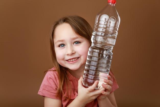 Klein meisje knuffelen een fles water