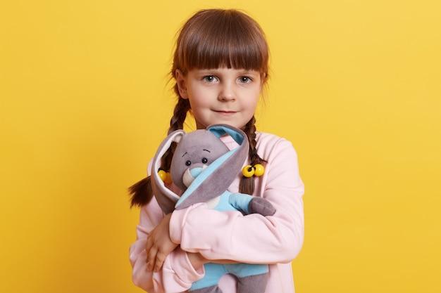 Klein meisje knuffelen haar zachte konijn, charmant vrouwelijk kind met vlechtjes liefde uitdrukken voor haar favoriete pluizige konijn tegen gele muur, kind spelen met speelgoed.