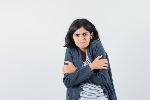 Klein meisje knuffelen zichzelf in t-shirt, jasje en op zoek nederig