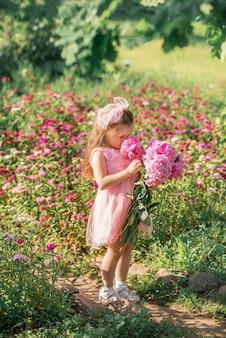 Klein meisje knuffelt een groot boeket pioenrozen. een kind met roze bloemen