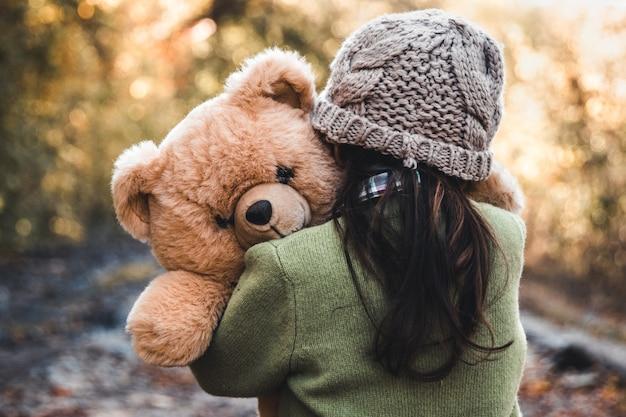 Klein meisje knuffelt haar beer op een achtergrond van de natuur, herfst, durba.