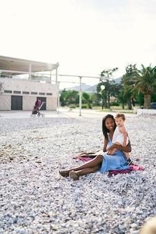 Klein meisje knuffelt moeder zittend op het strand