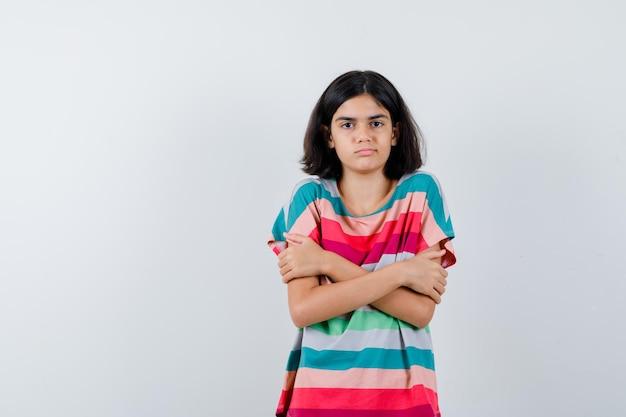 Klein meisje knuffelt zichzelf in t-shirt, spijkerbroek en ziet er serieus uit, vooraanzicht.