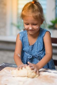 Klein meisje kookt thuis in de keuken
