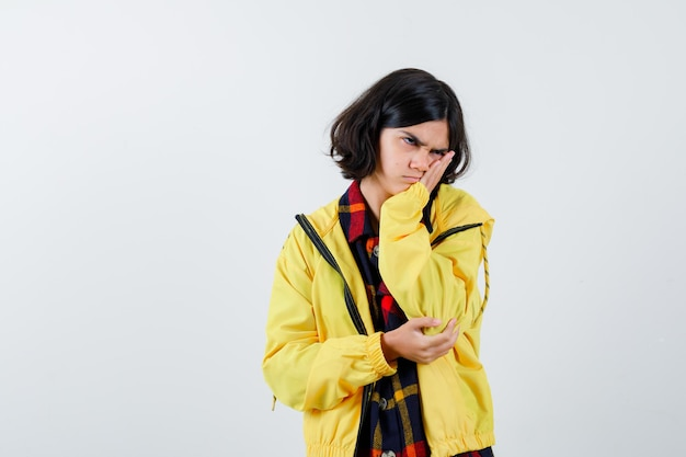 Klein meisje kussend gezicht op haar hand in geruit overhemd, jasje en weemoedig kijkend. vooraanzicht.