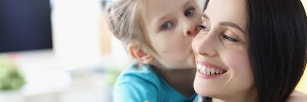 Klein meisje kust lachende moeder thuis