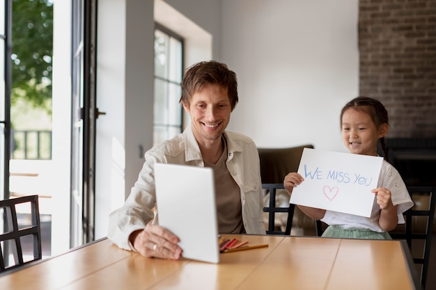 Klein meisje laat een ik mis je-bericht zien aan haar moeder tijdens een videogesprek