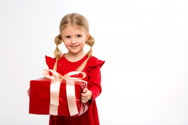 Klein meisje lachend met rode geschenk doos in de hand