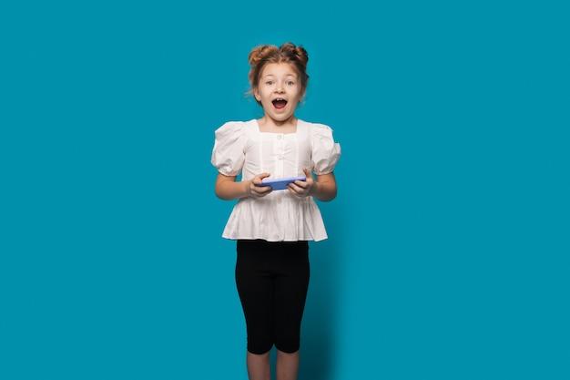 Klein meisje lacht met geopende mond terwijl ze een telefoon vasthoudt