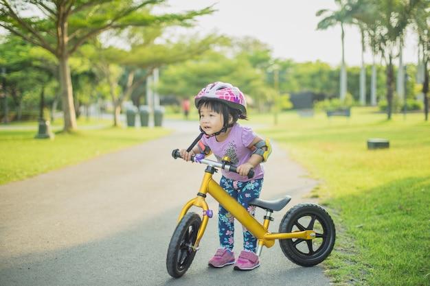 Klein meisje leert om te fietsen in het park
